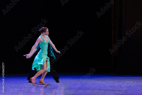 Photo A pair of dancers a man and a woman perform in a theater on stage in a dance musical show