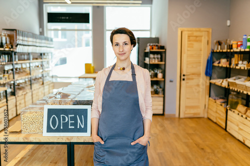 Reopening of a small business activity after the covid-19 emergency, ended the lockdown and quarantine. Business woman owner holding sign that says now we are open support local businesses.