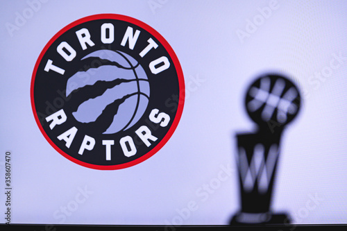 NEW YORK, USA, JUN 18, 2020: Toronto Raptors Basketball club on the white screen. Silhouette of NBA trophy in foreground.