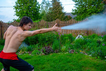 A Young Man On A Garden Plot Pretends To Let Out A Powerful Stream Of Water From His Hand.