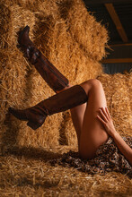 A Tanned Woman In A Leopard Print Dress And Boots Poses Lying On The Hay With Her Legs Raised. Legs Close Up. Inside The Barn