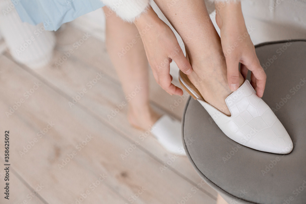 Fototapeta beautiful women's shoes on legs and layouts, leather white mules and loafers, in the interior of a room or office, a girl shoes, blue skirt and white shoes, a noble and elegant style, modern and trend