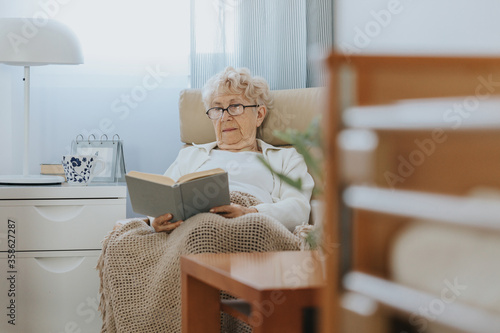 Senior woman sitting in armchair and reading book in nursing home #358627287