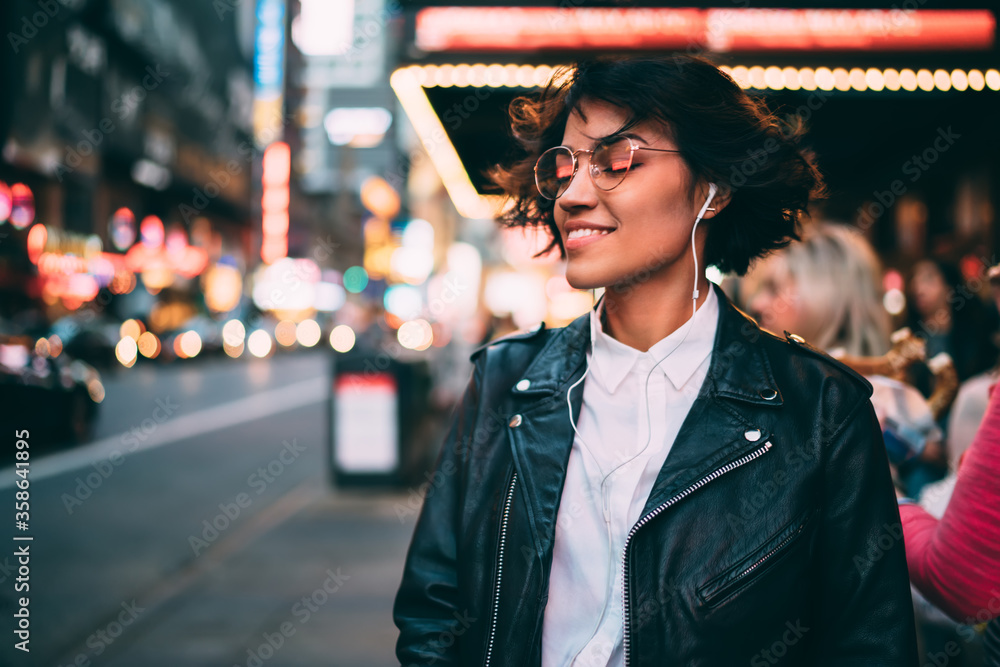 Fototapeta Carefree hipster girl in electronic headphones enjoying Ethno style of music podcast, happy female millennial in earphones listening positive audio playlist and smiling at metropolitan street