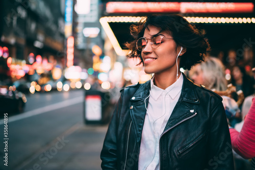 Obraz Carefree hipster girl in electronic headphones enjoying Ethno style of music podcast, happy female millennial in earphones listening positive audio playlist and smiling at metropolitan street - fototapety do salonu