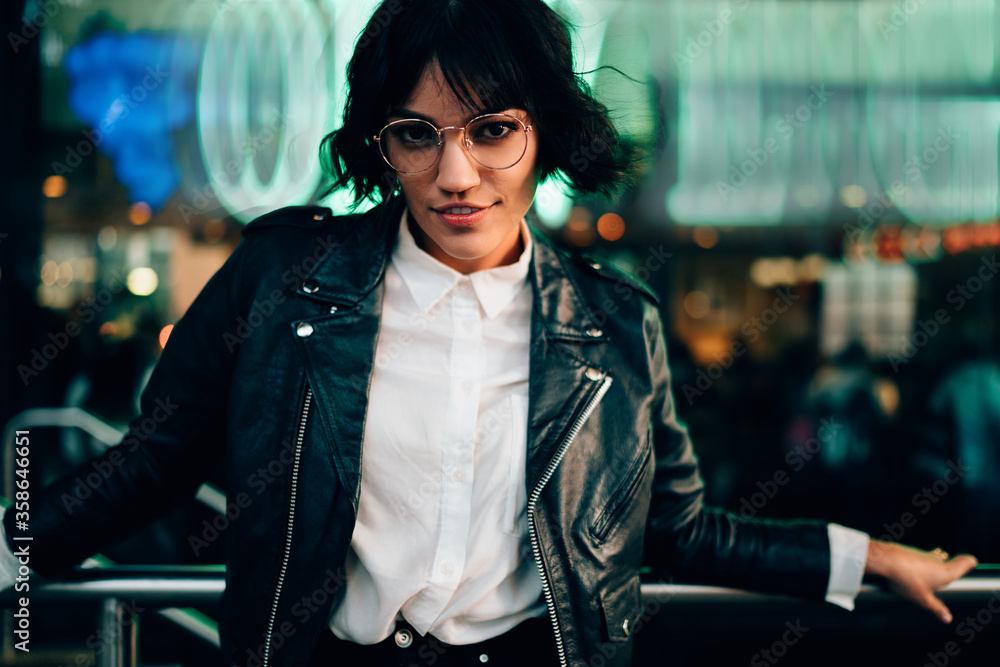 Fototapeta Half length portrait of attractive brunette hipster girl in eyeglasses dressed in casual stylish outfit looking at camera standing on blurred background in urban setting in evening leisure time