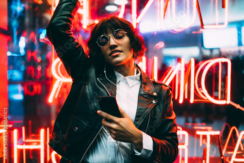 Carta da parati Beautiful brunette woman in trendy apparel and eyewear enjoying nightlife in city listening music in earphones and moving to sound, gorgeous hipster girl dancing outdoors on neon city illumination