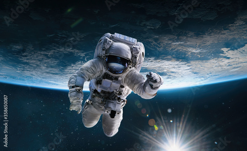 Obraz na płótnie Astronaut in the outer space with Sun over the planet Earth