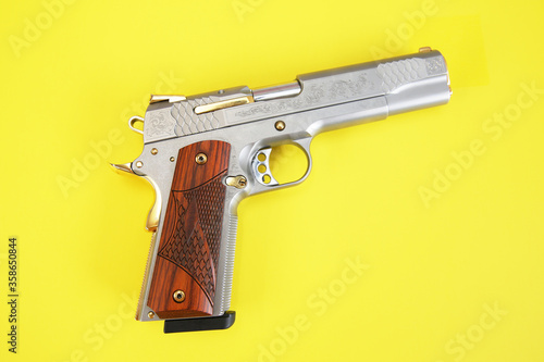 gun or pistol inlaid with wood and gold isolated on a yellow background Tapéta, Fotótapéta