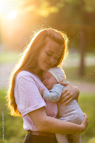 Fototapeta Young mother hugs a two-month-old newborn baby in the summer green park. Moments of happy motherhood obraz na płótnie