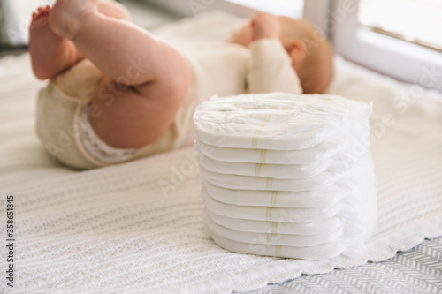 Fotografiet A baby in a diaper at the age of two months and a stack of diapers