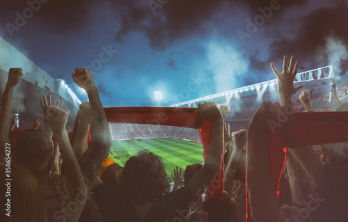 Photo Football scene at night match with with cheering fans at the stadium