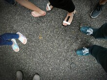 Top View Of Fee With Different Footwear On The Ground