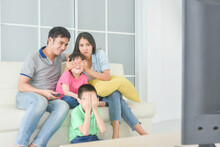 Asian Family Sitting On Sofa A...