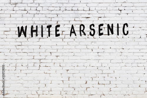 Photo White wall with black paint inscription white arsenic on it