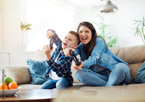 Fototapeta child son mother family happy playing console kid childhood joystick cotroller obraz