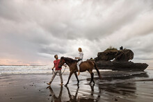 Asia, Indonesia, Bali, Young Caucasian Man With A Beautiful Young Caucasian Woman Sitting On A Horse, On A Beach At Sunset, With Typical Balinese Rock Formation Situated In The Sea