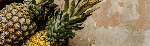 Obraz top view of ripe exotic pineapples on weathered surface, panoramic crop - fototapety do salonu