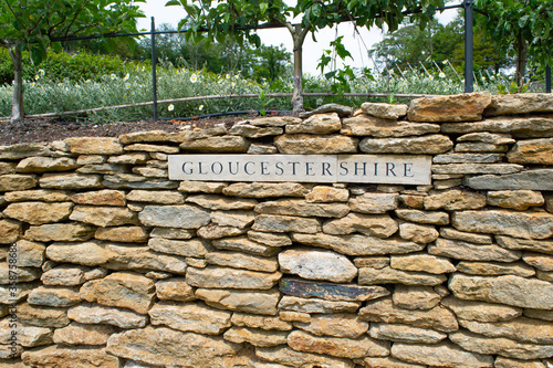 Fotografija A sign of the county of Gloucestershire set into dry stone wall in a garden
