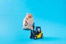 Picture Of Electric Loader Carrying Large Big Moneybag Sales Finance Management Interest Rate Pay Payment Isolated Over Bright Vivid Shine Vibrant Blue Color Background