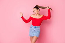 Photo Of Funky Crazy Carefree Lady Skinny Shape Arm Raise Long Tail Dancing Rejoicing Wear Casual Red Open Shoulders Shirt Mini Denim Skirt Isolated Pastel Pink Color Background