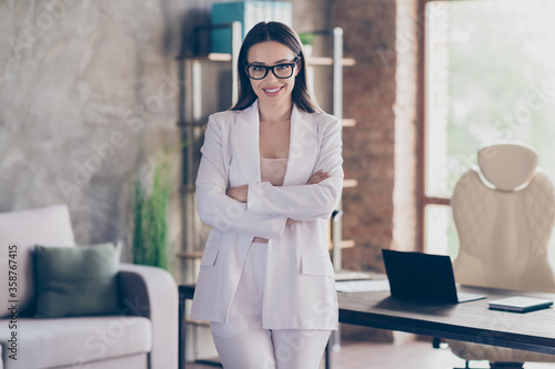 Portrait of her she nice-looking attractive pretty cheerful lady qualified shark investor real estate agency owner folded arms at modern industrial loft brick interior workplace workstation