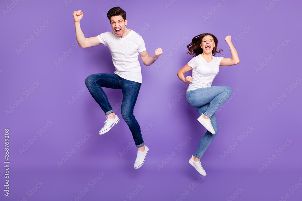 Fototapeta Full length photo pretty lady handsome guy couple jumping high up raise fists sporty competitions supporters fans wear casual t-shirts jeans pants shoes isolated purple color background