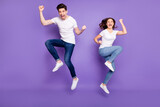Full length photo pretty lady handsome guy couple jumping high up raise fists sporty competitions supporters fans wear casual t-shirts jeans pants shoes isolated purple color background