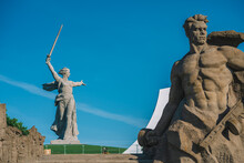 Beautiful Panorama Of The Monument To The Motherland On Mamayev Kurgan In The City Of Volgograd, In The Blue Sky The Trace Of The Plane