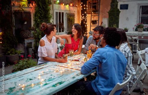 Obraz Young friends enjoy conversation at dusk - fototapety do salonu