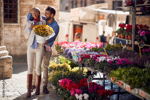 Fotografía man is surprising female with a bouquet of flowers holding her eyes closed in front of a flower shop