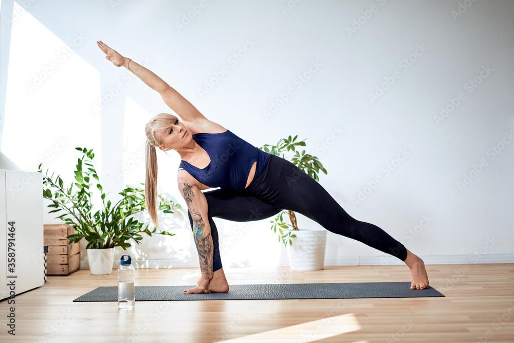 Fototapeta Fit woman exercise yoga at home