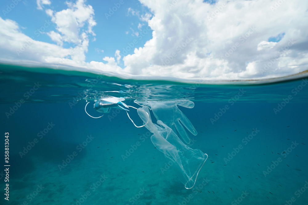 Fototapeta Plastic waste pollution in the sea since coronavirus COVID-19 pandemic, face mask with gloves underwater and sky with cloud, split view over and under water surface