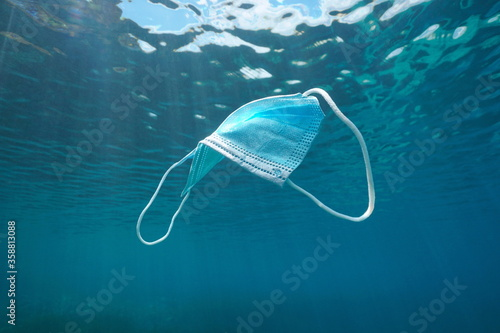 Fototapeta Disposable surgical face mask underwater, plastic waste in the ocean since coronavirus COVID-19 pandemic obraz