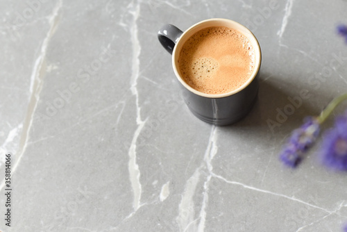 Fototapeta Coffee drink and flowers on a marble table in home interior obraz
