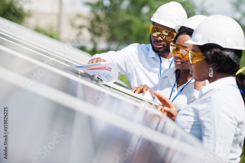 Obraz African american technician checks the maintenance of the solar panels. Group of three black engineers meeting at solar station. - fototapety do salonu