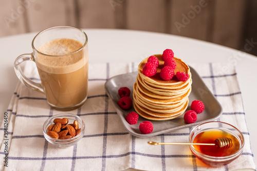 Fototapeta Mug with aromatic cappuccino, pancakes with raspberries, almond nuts and honey obraz