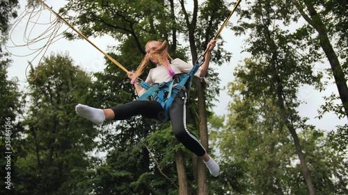 Fotografiet Teenage girl jumping on the trampoline bungee.