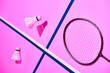 Leinwandbild Motiv Badminton shuttlecocks and racket on pink background with blue lines