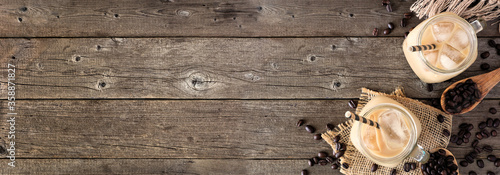 Fototapeta Cold iced coffee corner border over a rustic dark wood banner background with co