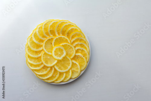 Photo Lemon cut into slices on a white plate