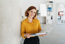 Attractive Young Office Worker Holding Large File