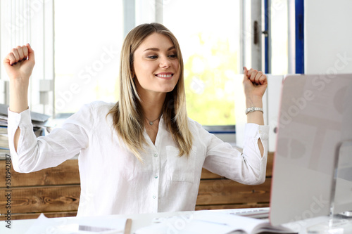 Foto Beautiful joyful woman at workplace using computer pc celebrate something with arms up