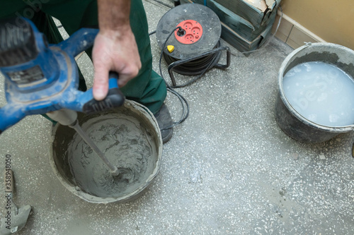 Photo A construction worker mixes an adhesive mortar in a black bucket with an electric device