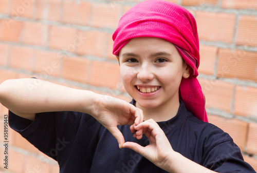 Fotografija girl with a headscarf for cancer making a heart symbol with her hands