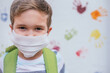 Child (5-7 years old) with mask and green backpack on a coloured background. Back to school concept