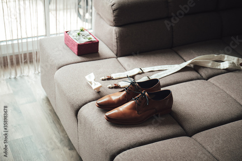 Fototapeta Men's accessories outfits. Brown formal leather shoes, bow-tie and suspenders prepared for dressing. Elements of groom's clothes laying on sofa. obraz