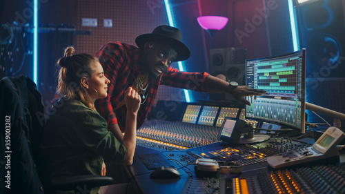 Producer and Professional Audio Engineer Working together in Music Recording Studio on a New Album, Talk, Use Control Desk Equalizer, Mixing Board and Software to Create Hit Song Fototapete