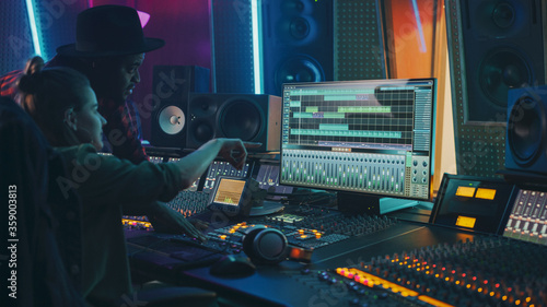 Producer and Professional Audio Engineer Working together in Music Recording Studio on a New Album, Talk, Use Control Desk Equalizer, Mixing Board and Software to Create Hit Song. Artist and Musician
