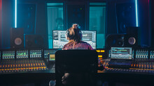 Artist, Musician, Audio Engineer, Producer In Music Record Studio, Uses Control Desk With Computer Screen Showing Software UI With Song Playing. Dances. Back View